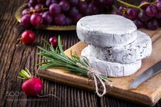 Camembert cheese with grape and branch of rosemary by AdrianMiiak