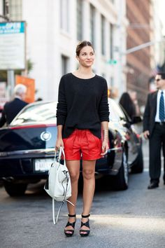 Maria Duenas tempers bold red leather shorts with an oversized sweater.