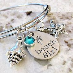 "This hand stamped bangle bracelet has a stamped pendant that measures 1"" x 3/4"" and is a pewter teardrop shape.  It is stamped ""Beach Girl"" and a palm tree!    An aqua channel set Swarovski crystal, Tibetan silver shell, and Tibetan silver starfish charm accents. Bangle is made of non-tarnishing stainless steel"