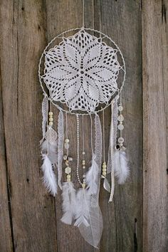 This one has a sleek and elegant design; from the crocheted string in the center to the white laces, buttons, beads and fluffy white feather hanging down.