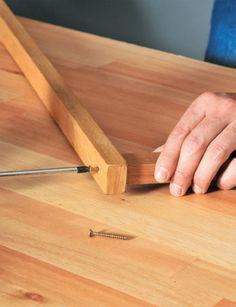 Antes que seque, use a chave de fenda para parafusar esse pedaço, com o lado de 3 cm voltado para cima, a um dos furos do sarrafo grande. Segure firme na posição até fixar. Faça o mesmo com o outro furo do sarrafo grande e repita este passo com as outras duas peças maiores.
