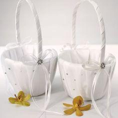 Betoverend satijnen mandje, in wit of ivoor! De handgrepen zijn opgesmukt met frivole strikken en 'n bloempje van parel en kristal. Vul het bloemenmandje met echte of zijden rozenblaadjes en laat uw bruidsmeisjes schitteren op deze dag.  Tip: u kan ook een gevuld bloemenmandje aan de uitgang van de ceremonielocatie zetten. Uw genodigden kunnen dan rozenblaadjes strooien als u als pasgetrouwd stel naar buiten komt. Ideaal alternatief voor het gooien van rijst.