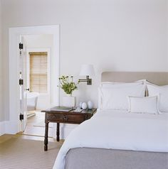Minimal bedroom with a vintage wooden bedside table, and a simple white sconce