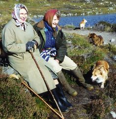 Corgis explore as Queen Elizabeth II and Margaret Rhodes rest during a trek through the deer-stalking area at Balmoral