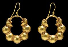 A PAIR OF EAST GREEK or ANATOLIAN GOLD HOOP EARRINGS   CLASSICAL PERIOD, CIRCA 5TH CENTURY B.C.   Each penannular, formed from five hollow spheres with hemispheres at the ends, the joins ornamented with double rows of granulation, the flat side of each hemisphere with a hinge to which is pinned the arching ear wire