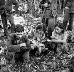 Exhausted Marianas Island civilians with wounded child after capture by (or surrender to) Americans during battle between US and Japanese forces for control of Saipan during WWII. July 1944.