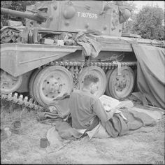 Crew members rest alongside a Cromwell tank of Armoured Brigade HQ, Armoured Divsion, 15 June