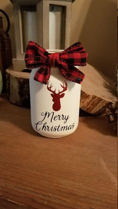 painted mason jars Pint size mason jar painted in ivory chalk paint Deer head is red glitter vinyl Merry Christmas is black vinyl Red and black buffalo plaid bow attached This jar ha Pint Mason Jars, Mason Jar Gifts, Mason Jar Diy, Small Mason Jars, Mason Jar Christmas Crafts, Merry Christmas, Christmas Diy, Mason Jar Centerpieces, Christmas Centerpieces