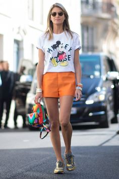 Helena Bordon playfully wears her Mickey Mouse tee tucked into orange shorts.