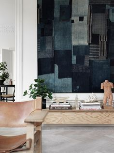 Living space with a wood and leather chair, white walls, and mixed-medium art work