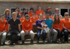 The Urban Saints group pictured in front of the house they built, along with the family who will be living there and a team from Kirkby Lonsdale.