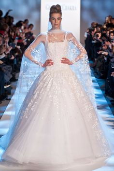 Georges Chakra Couture spring/summer 2013  The ever-popular princess line wedding gown got an update at Georges Chakra, with a sheer cloak of printed tulle swathed accross the shoulders before it cascaded down the back. The floral motif was echoed on the skirt of the dress