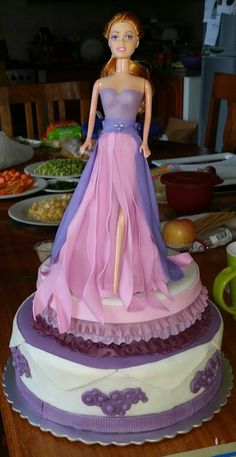 My first fondant barbie cake. This is made of three-tier chocolate cake, the top cake is a small round cake, sloped just under barbies butt to support her upright.