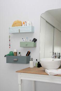 Ici encore, on investit les murs de la salle de bain en installant des petits rangements futés et ultra déco. Facilement réalisable et représentant une solution rangement pas chère, il vous suffit de récupérer les tiroirs d'un vieux petit meuble, de les couper pour en réduire la profondeur, de les peindre de la couleur souhaitée et enfin de les fixer de façon déco aux murs. Et voilà des rangements colorés pour stocker tous vos petits produits de toilette dans la salle de bain !