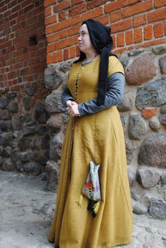 Medieval outfit based on Flemish illuminations from the 1st half of the 15th century, depicting women in town. Linen chemise, woollen hose, leather shoes, cotte simple of grey wool and over kirtle of yellowish-orange wool, linen st Birgitte's cap, open hood of black wool, girdle with accessories. All part completely hand-sewn.