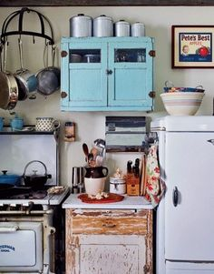 Vintage kitchen. I love the weathered cabinet below and the splash of color the turquoise cabinet above. by connie