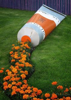 Orange flowers spilling from a huge paint tube.