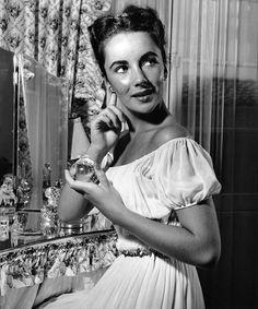 Elizabeth Taylor puts on perfume,1947.