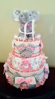 Pink and gray baby girl elephant diaper cake.  Just precious! Baby shower gift/ centerpiece. Check out my Facebook page Simply Showers for more pics and orders.  https://m.facebook.com/adorablegifts  www.TopsyTurvyDiaperCake.com - washcloth favors, washcloth animals, diaper cakes, and baby shower gifts