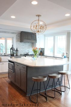Beautiful kitchen remodel before and afters - gray kitchen island with white cabinets.