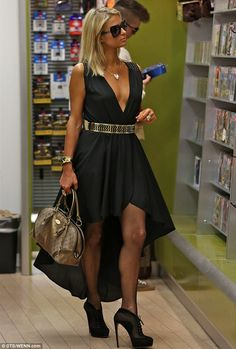 Paris Hilton in a plunging black dress at the LAX airport for a long-haul flight to Barcelona