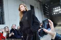 Snap happy: Gigi was captured by an array of onlookers with their mobiles...