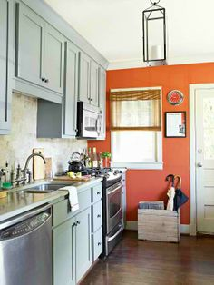Consider a color that's complementary to the colors already found in your kitchen. Here, a coral-orange paint complements the dusty-blue cabinets.