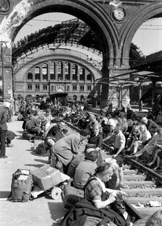Margaret Bourke-White, People sitting on railroad tracks in the destroyed terminal station Anhalter Bahnhof, Berlin, Germany, 1945
