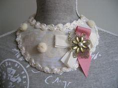 Cuello de tela con lazos, aplique floral en color bronce, pompones y pasamanería en ondas.