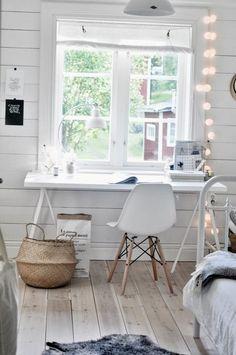 petit bureau scandinave blanc aménagé avec une table blanche, une chaise Eames blanche et une guirlande lumineuse