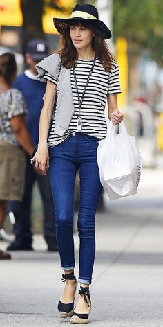 Alexa Chung wearing a stripped top, blue jeans, and a cute black hat.