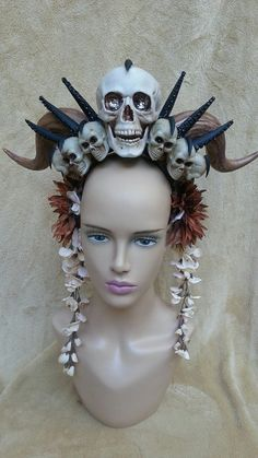 This headdress has 1 large skull and six lil skulls worked around horns and finished with flowers and trim. There are 2 variations to this