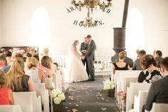 Bride and groom exchanging vows in modern church @myweddingdotcom