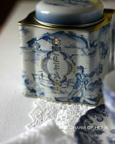 """vintage looking blue and white tin labelled """"TEA"""" with toile-like pastoral scene, serpentine square shape with cap lid,"""