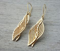 A stunning element inspired by aquatic themes. A ripples shaped pattern dangles from an elegant earwire. Made of high quality 24K gold or silver