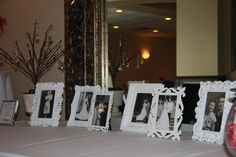 Wedding Photos/In Remembrance. In honor of the parents and grandparents of the bride & groom, their wedding photos were placed in in different white frames.  To the left is a light up branch with crystals hanging from the branches (each representing loved ones lost).  Their names were printed in a frame and place in front of the display.