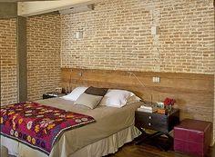 Em vez de um modelo tradicional, a arquiteta Flavia Petrossi optou por revestir a parede atrás da cama com um lambri de madeira de demolição. A solução conversa com os tijolos aparentes e acrescenta textura ao quarto do casal.