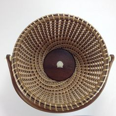 Heirloom quality Nantucket Lightship Basket made of hand-pounded black ash that is woven over walnut in a complex spiral pattern. This updated version of the traditional Lightship features a complex spiral weave pattern that is based on the Fibonacci Number Sequence. Basket is 8 in diameter and 6 tall (12 with swing handle in up position). The handle is secured with solid brass carriage bolts inserted through bone knobs and spacers. Shell carving and base insert are also bone. The base…