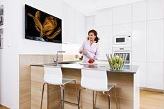 Bílá kuchyň značky Hanák v minimalistickém provedení bez úchytek, s hladkými lesklými plochami a s ostrůvkem s šedou corianovou pracovní deskou nabízí praktické a nadčasové řešení, které se shoduje se vkusem Dany Morávkové