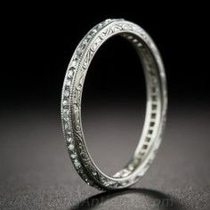 "About as fine and fabulous as they come in an original Art Deco diamond wedding band. This slender (2.4 mm. or about 3/16"") beauty, expertly hand-fabricated in platinum during the roaring '20s, sparkles all around with seamlessly-set French-cut diamonds accentuated with fine milgrain edges and intricately hand-engraved sides. A superlative, rare and pristine accompaniment to vintage engagement ring from Lang. Size 7 1/2 now and forever."