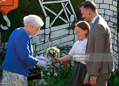 Britain's Queen Elizabeth II (L) reacts as is present with a posy of flowers by Caitlyn James from Swansea at the Chelsea Flower Show in London on May 22, 2017. The Chelsea flower show, held annually in the grounds of the Royal Hospital Chelsea, opens to the public this year from May 22. /