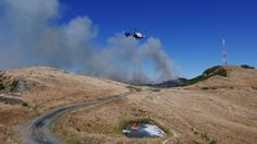 A helicopter fills a monsoon bucket from a small pond near Sugarloaf on the Port Hills. Small Ponds, Monsoon, Destruction, Rage, New Zealand, Bucket, Country Roads, Adventure, Adventure Movies
