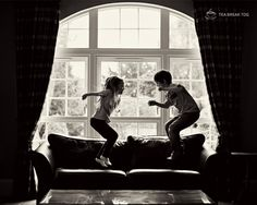 Kids jumping up and down on couch in front of a large window.