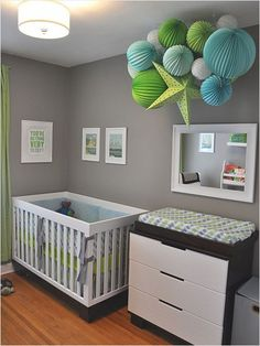 Geometric Cool: beautiful paper lantern/mobile sculpture hanging over baby's changing table in this Minnesota nursery. What an amazing, stimulating piece for baby (and mama) to look up at! DIY Tip: Buy a few packs of inexpensive paper lanterns ($7.95 for a set of 8 at Amazon) that match your room palette and group together different shapes and sizes. Hang from a ceiling hook with fishing line.