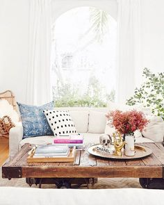 Feminine, eclectic dining room. Rustic coffee table, rattan chair with fur throw, blue textiles, pop of pink.