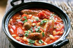 Sausage Casserole Recipe Main Dishes with olive oil, sausages, onions, garlic cloves, leeks, medium potatoes, smoked paprika, plum tomatoes, red wine, beef stock, cannellini beans, salt, pepper, flat leaf parsley, crusty bread