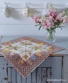 Soft pastel florals and olive green and lavender prints welcome spring in the simple appliqué quilt.