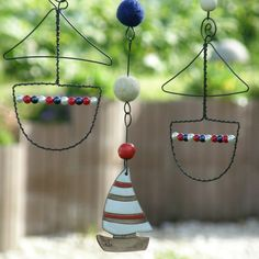 Wired curtain of black iron wire with a ceramic boat, wooden rings, wooden beads and felt bullets. Iron Wire, Wooden Rings, Wire Crafts, Wire Art, Hot Air Balloon, Wooden Beads, Metal, Balloons, Ceramics