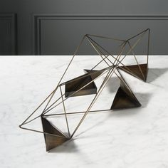 Shop wireplay candle holder.   Prismatic sculpture angles five flickers in a graphic play of light and shadow.  Antiqued iron intersects open/closed geometric planes, projecting light from every direction.