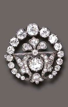 AN ANTIQUE DIAMOND BROOCH The openwork old European and old mine-cut diamond circular plaque, centering upon a similarly-set foliate motif, to the central old European-cut diamond accent, mounted in silver, (with hook for suspension), circa 1880
